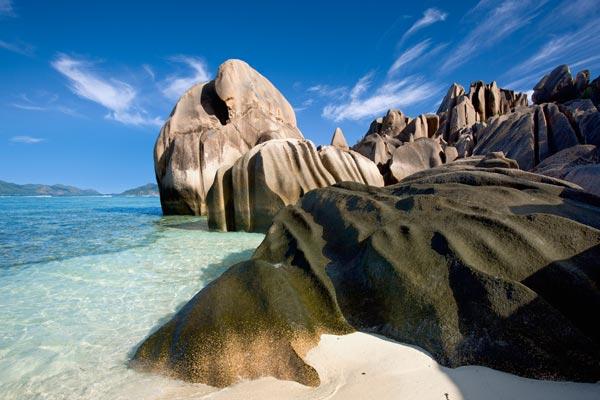 Azure lagoon lapping granite boulder.
